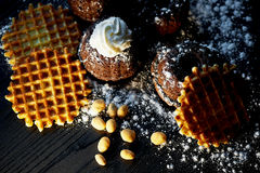 Lush fresh chocolate muffins sprinkled with powdered sugar, lay against the dark wood. Round Belgian waffles. Also have Stock Photos