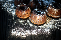 Lush fresh chocolate muffins sprinkled with powdered sugar, lay against the dark wood.Studio Stock Photo