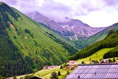 Lush green alpine peaks and valley with the roofs of chalets in the foreground in Berwang, Tirol Stock Photography