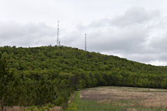 Lush green foliage on mountain side with various towers atop. Green mountain side with various towers overlooking open meadow Stock Images