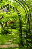 Lush green garden. With wrought iron arbor Stock Images
