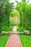Lush green garden with wrought iron arbor.  Royalty Free Stock Image