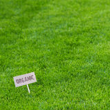 Lush green grass background with Organic sign. Lush green grass background wit an Organic sign facing the camera in the bottom left corner conceptual of the Stock Photo