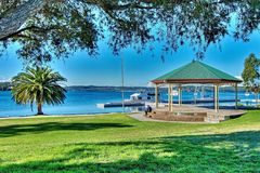 Lush green grassy waterfront park with a quaint little old Band. Gazebo - Bandstand in a lush green grassy waterfront park with trees and an occupied boat jetty Stock Photography