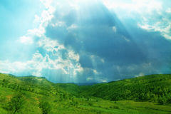 Lush, green landscape with sun shining through clouds. royalty free stock photo