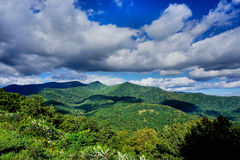 Lush green mountain and blue sky Royalty Free Stock Image