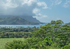 Lush Land and Blue Sea. Hanalei bay on a cloudy day, with mountains and lush green landscape, on Kauai Stock Photography