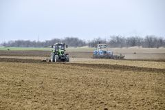 Lush and loosen the soil on the field before sowing. The tractor plows a field with a plow.  Royalty Free Stock Photos