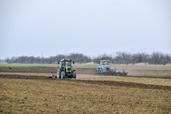 Lush and loosen the soil on the field before sowing. The tractor plows a field with a plow.  Stock Photography