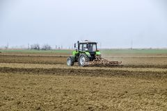 Lush and loosen the soil on the field before sowing. The tractor plows a field with a plow.  Royalty Free Stock Image