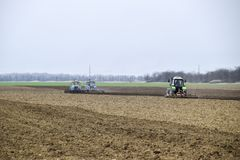 Lush and loosen the soil on the field before sowing. The tractor. Plows a field with a plow Stock Photos