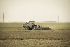 Lush and loosen the soil on the field before sowing. The tractor plows a field with a plow.  Royalty Free Stock Photo