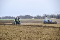 Lush and loosen the soil on the field before sowing. The tractor plows a field with a plow.  Stock Photos
