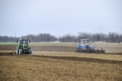 Lush and loosen the soil on the field before sowing. The tractor plows a field with a plow.  Royalty Free Stock Photography