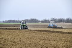 Lush and loosen the soil on the field before sowing. The tractor plows a field with a plow.  Stock Photo