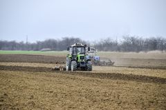 Lush and loosen the soil on the field before sowing. The tractor plows a field with a plow.  Royalty Free Stock Images