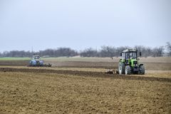 Lush and loosen the soil on the field before sowing. The tractor plows a field with a plow.  Stock Image