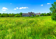 Lush overgrown field with deserted farmhouse Royalty Free Stock Photos