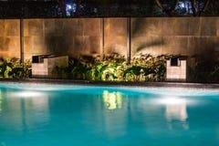 Lush pool lighting in backyard for luxury swimming pool design c Royalty Free Stock Photo