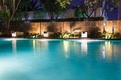Lush pool lighting in backyard for luxury swimming pool design c Stock Image