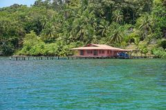 Lush tropical coast with house and dock over the sea Stock Photos