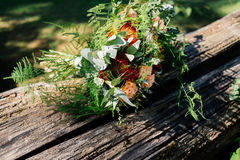 Lush wedding bouquet on a gray wooden bench. Near the water Stock Image