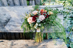 Lush wedding bouquet on a gray wooden bench near the water. With water lily Stock Photography