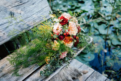 Lush wedding bouquet on a gray wooden bench near the water. With water lily Stock Image