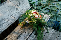 Lush wedding bouquet on a gray wooden bench. Near the water with water lily Stock Photos