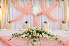 Lush wedding floral decorations on dinner table. Covered with peach cloth. Table for the newlyweds Royalty Free Stock Photos