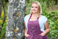 Lush woman in apron with hands in her pockets leaning birch Royalty Free Stock Photo