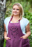 Lush woman in apron with hands in her pockets standing near tree Royalty Free Stock Image