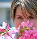 Lust. An attractive woman peaks her head over some flowers looking with a seductive way Stock Image