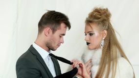 Lust, passionate look, guy in black suit trying to kiss blonde girl with dark lips wearing white fur coat, lady pulling. Lust, passionate look, guy with bristle stock footage