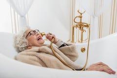 Lustige ältere Dame mit Pelzmantel in der Badewanne Lizenzfreie Stockfotografie