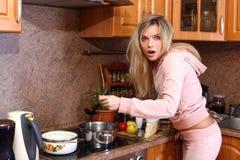 Lustige überraschte Frau, die Abendessen kocht Lizenzfreies Stockbild