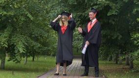 Lustige Absolvent in den akademischen Kleidern, die herum nach Staffelung tanzen und täuschen stock footage
