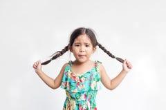 Lustige Aktion des asiatischen Mädchenspiels mit ihrem Ponyhaar lizenzfreies stockbild