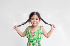 Lustige Aktion des asiatischen Mädchenspiels mit ihrem Ponyhaar stockfotos