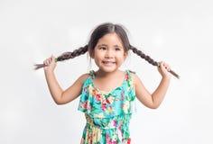 Lustige Aktion des asiatischen Mädchenspiels mit ihrem Ponyhaar lizenzfreie stockfotos