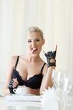 Lustige attraktive Blondine, die bei Tisch Gesicht verzieht Lizenzfreie Stockfotografie