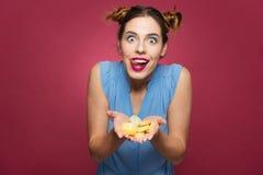 Lustige aufgeregte Frau, die Geleesüßigkeiten hält und Zunge zeigt Lizenzfreie Stockbilder