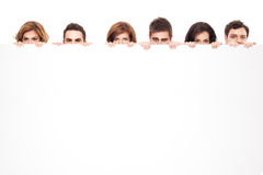 Lustige Augen, die hinter whiteboard spähen Stockfotografie