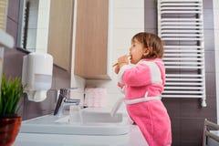 Lustige bürstende Zähne des kleinen Mädchens im Bad obacht Hygiene lizenzfreies stockbild
