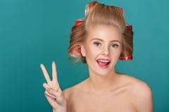 Lustige blonde Frau über blauem Hintergrund Stockfotografie
