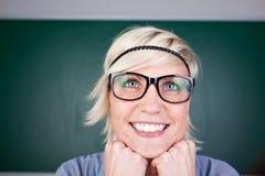 Lustige blonde Frau, die gegen Tafel lacht Stockbild
