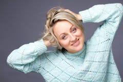 Lustige blonde Frau in einer Winterstrickjacke Lizenzfreies Stockfoto