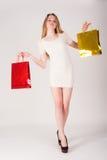 Lustige blonde Frau mit Einkaufstaschen Lizenzfreie Stockbilder
