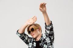 Lustige blonde hübsche tragende Sonnenbrille des jungen Mannes und wellenartig bewegende Hände des zufälligen Tanzens des kariert Lizenzfreies Stockfoto
