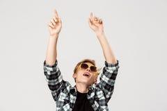 Lustige blonde hübsche tragende Sonnenbrille des jungen Mannes und wellenartig bewegende Hände des zufälligen Tanzens des kariert Stockfotografie